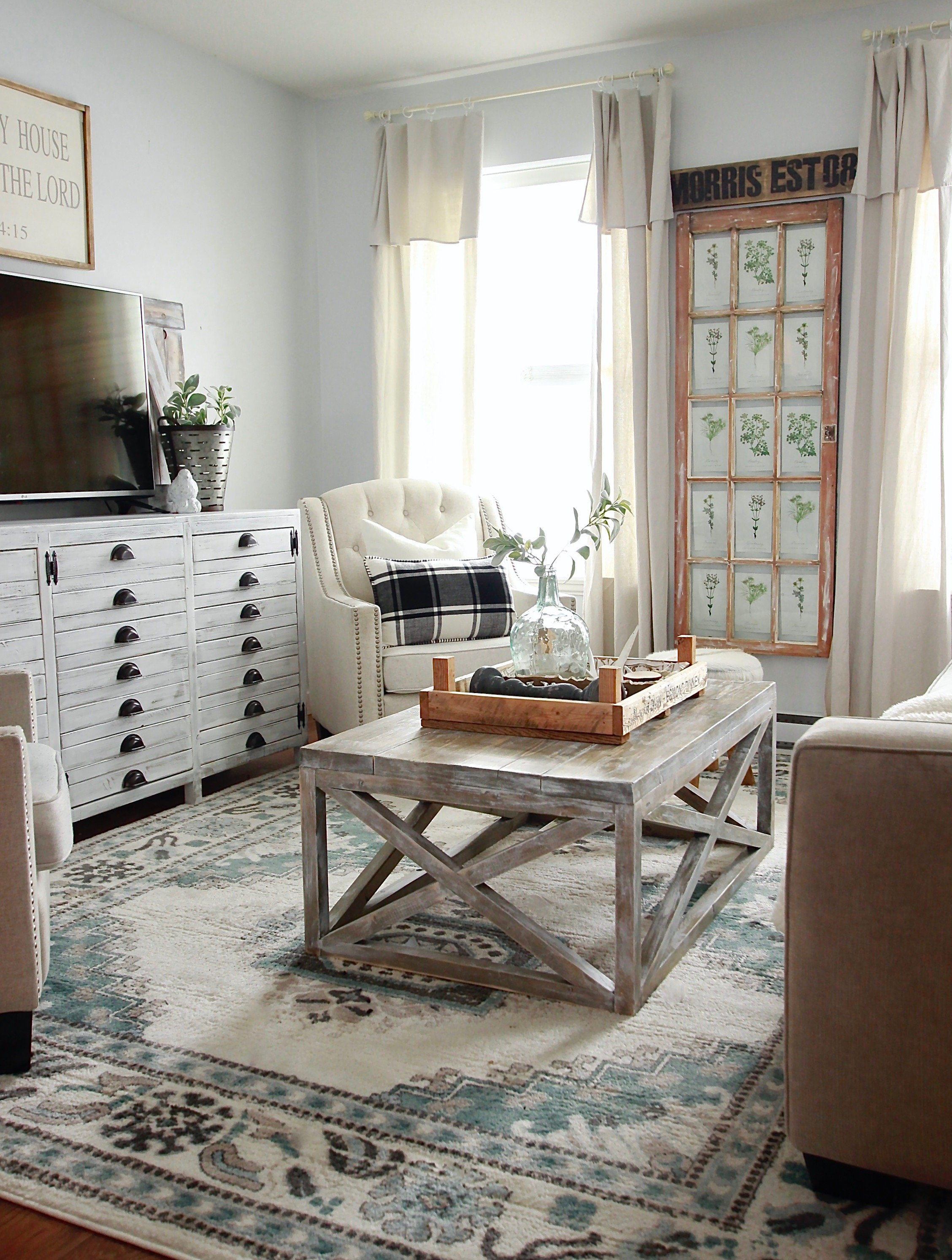 White Farmhouse Living Room with Distressed Rustic Coffee Table and Sage Accents www.whitepicketfarmhouse.com