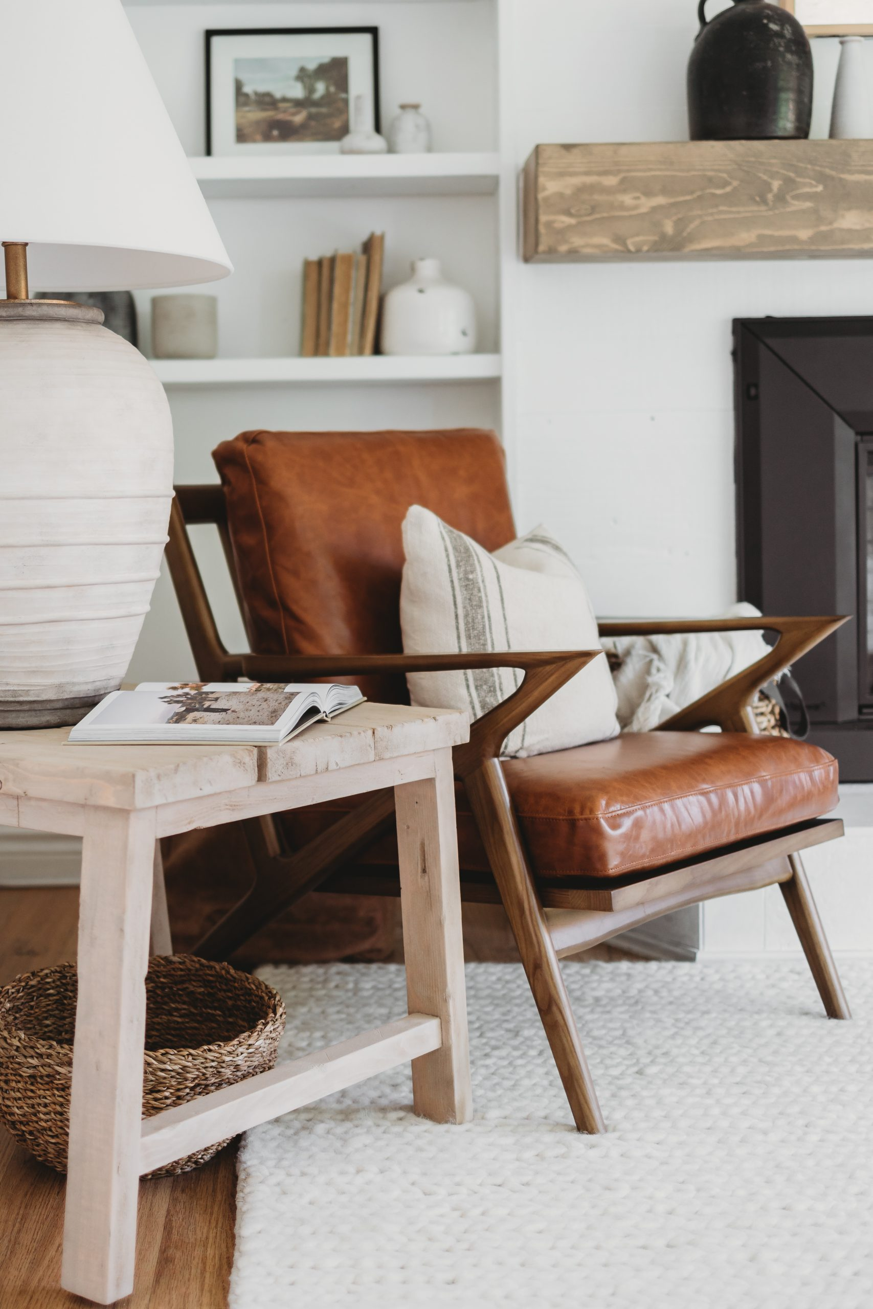 Updated Modern Coastal Living Room. How we styled our Kavuus sectional and leather chairs as well as our vintage artwork and Samsung frame TV on our white shiplap fireplace.
