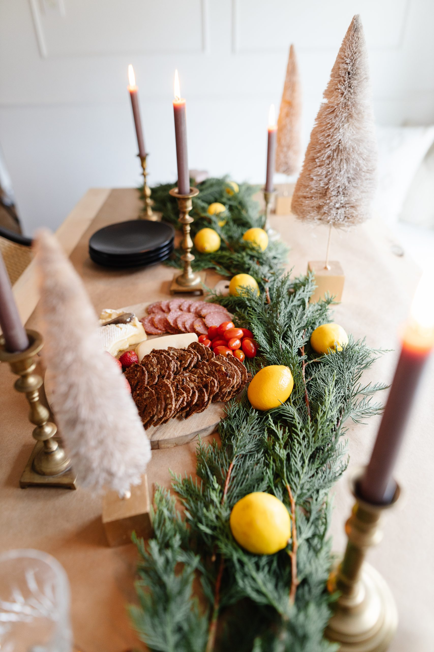 How to create a vintage Christmas tablescape. I used items we already had with vintage crystal glass, candlesticks and even an old quilt! I blended modern pieces with traditional pieces to give our Christmas dining room a very cozy feel. I used taupe candles with brass candlesticks to make the space feel inviting. Holiday decorating doesn't have to be uniform - make it fun!